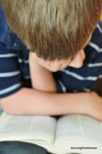Boy leaning over Bible.