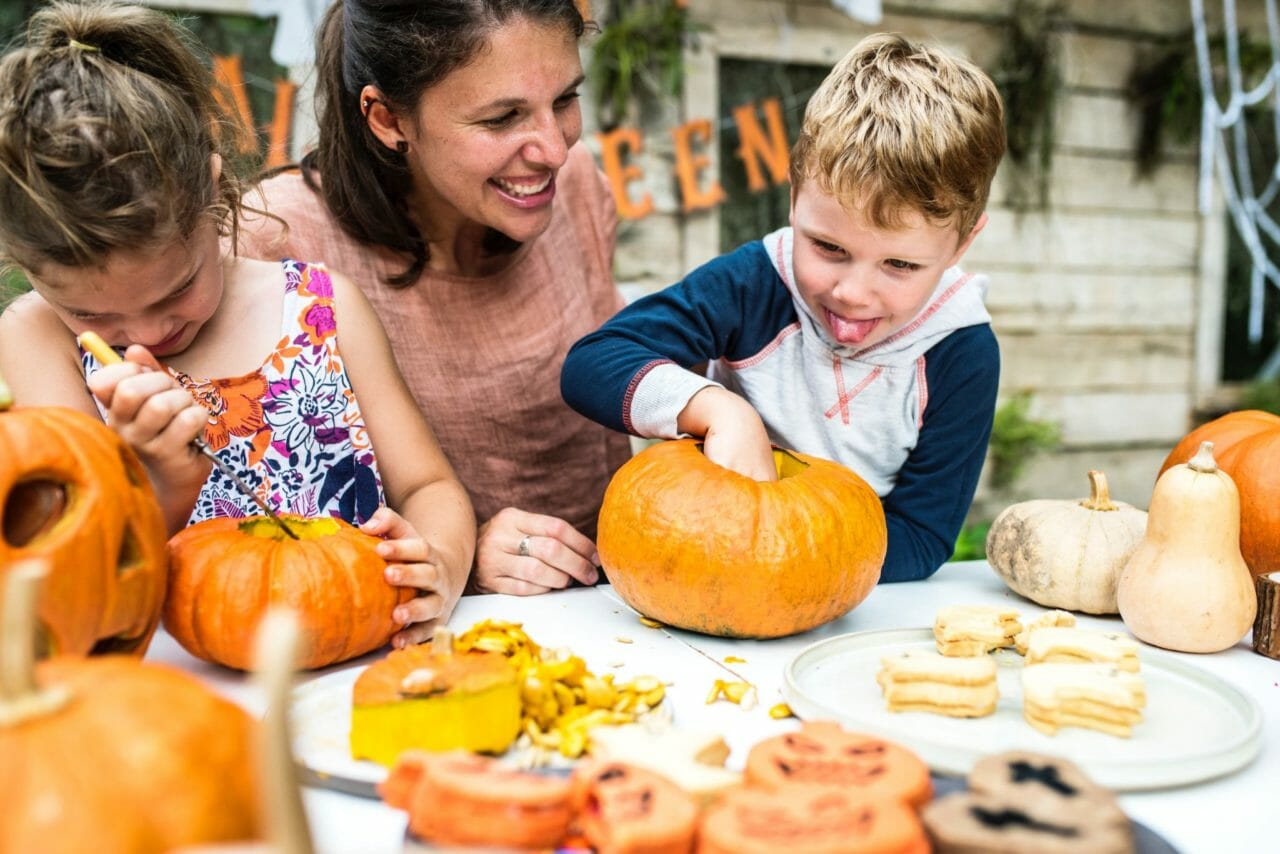 mom and children carving pumpkins