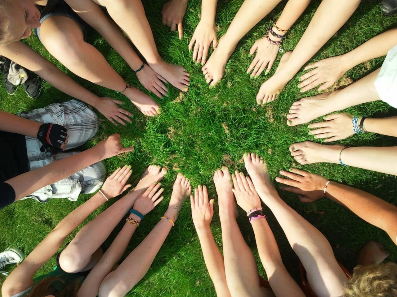 group of kids with hands and feet in circle